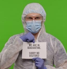 medical professional holding no visitors sign